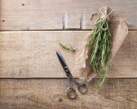 Aromatische takjes van rozemarijn, schaar op het hout stock foto