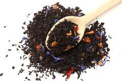 Aromatische zwarte droge thee met bloemblaadjes in houten die lepel op witte achtergrond wordt geïsoleerd Royalty-vrije Stock Foto's