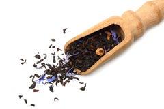 Aromatische zwarte droge thee met bloemblaadjes in houten die lepel op witte achtergrond wordt geïsoleerd Stock Foto