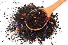 Aromatische zwarte droge thee met bloemblaadjes in houten die lepel op witte achtergrond wordt geïsoleerd Royalty-vrije Stock Afbeelding