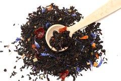Aromatische zwarte droge thee met bloemblaadjes in houten die lepel op witte achtergrond wordt geïsoleerd Royalty-vrije Stock Fotografie