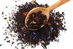 Aromatische zwarte droge thee met bloemblaadjes in houten lepel op witte achtergrond Stock Foto