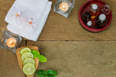 Aromatisches Öl in der hölzernen Schüssel des Schmutzes, gebrannt Kerze, rosa Blumen, geschnittener Kalk, grünes Blatt, weißes Tu Lizenzfreies Stockbild