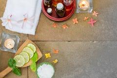 Aromatisches Öl in der hölzernen Schüssel, gebrannt Kerze, gelb-orangee Blumen des Rosas, schnitt Kalk, grünes Blatt, weißes Tuch Stockbilder