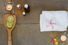 Aromatisches Öl, gebrannt Kerze, Rosagelb, orange Blumen, geschnittener Kalk, weißes Tuch auf Weinleseschmutz-Steinhintergrund Stockbild