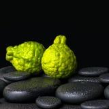 Aromatisches Badekurortkonzept der Bergamotte trägt auf Zenbasaltschwarzes ston Früchte Lizenzfreie Stockfotografie