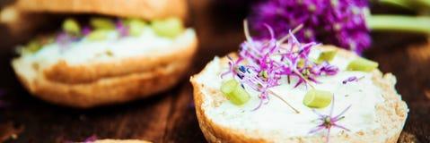 Aromatisk smörgås med ägget, makrillen och ätliga blommor av gräslökar royaltyfria foton