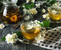 Aromatiskt varmt jasminte i kokkärl och koppar, nära skedar Arkivbilder