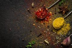 Aromatizza il fondo dell'alimento intere di varietà di selezione e spezie a terra asciutte su un fondo nero Immagini Stock