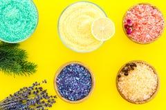 Aromaty kąpielowa sól Cytryna, kawa, rozmaryn, wzrastał, lawendowi pobliscy puchary z kolorową kąpielową solą na żółtym tło wierz zdjęcie royalty free
