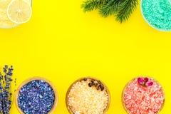 Aromaty kąpielowa sól Cytryna, kawa, rozmaryn, wzrastał, lawendowi pobliscy puchary z kolorową kąpielową solą na żółtym tło wierz zdjęcia stock