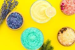 Aromaty kąpielowa sól Cytryna, kawa, rozmaryn, wzrastał, lawendowi pobliscy puchary z kolorową kąpielową solą na żółtym tło wierz zdjęcia royalty free