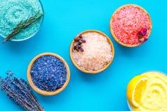 Aromaty kąpielowa sól Cytryna, kawa, rozmaryn, wzrastał, lawendowi pobliscy puchary z kolorową kąpielową solą na błękitnym tło wi zdjęcie stock