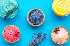 Aromaty kąpielowa sól Cytryna, kawa, rozmaryn, wzrastał, lawendowi pobliscy puchary z kolorową kąpielową solą na błękitnym tło wi fotografia royalty free