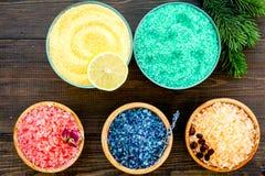 Aromaty kąpielowa sól Cytryna, kawa, rozmaryn, wzrastał, lawendowi pobliscy puchary z kolorową kąpielową solą na ciemny drewniany obraz royalty free