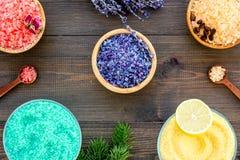Aromaty kąpielowa sól Cytryna, kawa, rozmaryn, wzrastał, lawendowi pobliscy puchary z kolorową kąpielową solą na ciemny drewniany fotografia stock