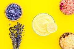 Aromaty kąpielowa sól Kawa, wzrastał, lawendowi pobliscy puchary z kolorową kąpielową solą na żółtego tła odgórnym widoku zdjęcie stock