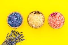 Aromaty kąpielowa sól Kawa, wzrastał, lawendowi pobliscy puchary z kolorową kąpielową solą na żółtej tło odgórnego widoku kopii p zdjęcia royalty free