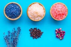 Aromaty kąpielowa sól Kawa, wzrastał, lawendowi pobliscy puchary z kolorową kąpielową solą na błękitnego tła odgórnym widoku zdjęcia royalty free