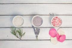 Aromaty kąpielowa sól Wzrastał, lawenda i sosnowi pobliscy puchary z kolorową kąpielową solą na lekkiej drewnianej tło odgórnego  zdjęcie stock