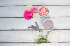 Aromaty kąpielowa sól Wzrastał, lawenda i sosnowi pobliscy puchary z kolorową kąpielową solą na lekkiej drewnianej tło odgórnego  obraz royalty free