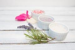 Aromaty kąpielowa sól Wzrastał, lawenda i sosnowi pobliscy puchary z kolorową kąpielową solą na lekkiej drewnianej tło odgórnego  fotografia royalty free