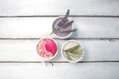 Aromaty kąpielowa sól Wzrastał, lawenda i sosnowi pobliscy puchary z kolorową kąpielową solą na lekkiej drewnianej tło odgórnego  zdjęcia stock
