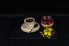 Aromatyczna czarna kawa w filiżance śmietankowy, słodki truskawkowy desse, zdjęcia royalty free