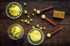 Aromatyczna zdrój sól Żółta zdrój sól z delikatną wiosną kwitnie na ciemnego drewnianego tła odgórnym widoku Fotografia Stock