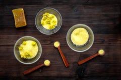 Aromatyczna zdrój sól Żółta zdrój sól z delikatną wiosną kwitnie na ciemnego drewnianego tła odgórnym widoku Zdjęcie Stock