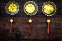 Aromatyczna zdrój sól Żółta zdrój sól z delikatną wiosną kwitnie na ciemnego drewnianego tła odgórnym widoku Obraz Stock
