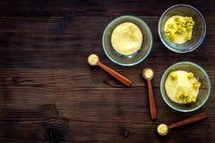 Aromatyczna zdrój sól Żółta zdrój sól z delikatnymi wiosna kwiatami na ciemnej drewnianej tło odgórnego widoku kopii przestrzeni Obraz Royalty Free