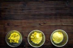 Aromatyczna zdrój sól Żółta zdrój sól z delikatnymi wiosna kwiatami na ciemnej drewnianej tło odgórnego widoku kopii przestrzeni Fotografia Stock