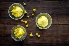 Aromatyczna zdrój sól Żółta zdrój sól z delikatnymi wiosna kwiatami na ciemnej drewnianej tło odgórnego widoku kopii przestrzeni Obrazy Stock