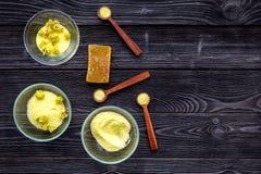 Aromatyczna zdrój sól Żółta zdrój sól z delikatnymi wiosna kwiatami na czarnej drewnianej tło odgórnego widoku kopii przestrzeni Obraz Stock