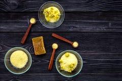 Aromatyczna zdrój sól Żółta zdrój sól z delikatnymi wiosna kwiatami na czarnej drewnianej tło odgórnego widoku kopii przestrzeni Obrazy Royalty Free