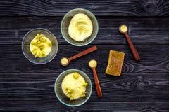 Aromatyczna zdrój sól Żółta zdrój sól z delikatnymi wiosna kwiatami na czarnej drewnianej tło odgórnego widoku kopii przestrzeni Zdjęcia Royalty Free