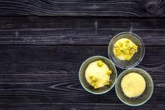 Aromatyczna zdrój sól Żółta zdrój sól z delikatnymi wiosna kwiatami na czarnej drewnianej tło odgórnego widoku kopii przestrzeni Fotografia Royalty Free