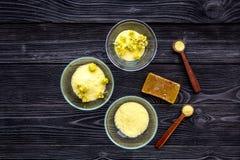 Aromatyczna zdrój sól Żółta zdrój sól z delikatnymi wiosna kwiatami na czarnej drewnianej tło odgórnego widoku kopii przestrzeni Zdjęcie Royalty Free