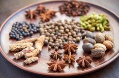 Aromatyczne pikantność na zmroku talerzu - gwiazdowy anyż, fragrant pieprz, tatarakowy korzeń, cynamon, nutmeg zamknięty up na br Fotografia Royalty Free