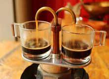 Aromatyczny kawowy ciurkanie od za mini retro piwowarstwo garnku w parę szkła demitasse filiżanki zdjęcie stock