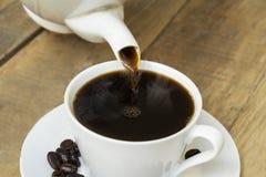 Aromatyczny kawowy dolewanie w filiżankę na stole fotografia stock
