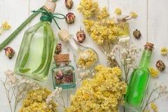 Aromatyczny olej, aromatyczni ziele w szklanych butelkach na drewnianym tle, Pojęcie ciała piękno i opieka zdjęcia royalty free