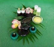 Aromatyczny olej, sól, świeczki, kamienie i kwiat, obraz stock