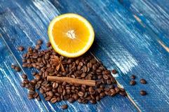 Aromatyczny skład pomarańcze, cynamon i kawowe fasole na zmroku, - błękitny tło Odgórny widok fotografia stock