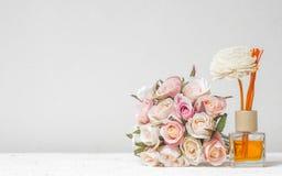 Aromatyczny trzcinowy freshener, woń dyfuzor Ustawiający butelka z aromatów kijów trzcinowymi dyfuzorami z róża kwiatem na biel ś fotografia stock