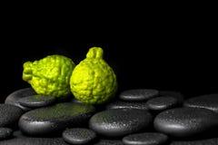 Aromatyczny zdroju pojęcie bergamotowe owoc na zen bazaltowym czarnym ston zdjęcie royalty free