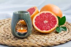 Aromlampa med nödvändig olja för grapefrukt, brunnsortbakgrund som är horisontal Royaltyfri Fotografi