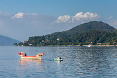 ARONA, ITALY/ EUROPE - SEPTEMBER 17: Rowing boat pulling a tradi. Tional boat on Lake Maggiore Piedmont Italy on September 17, 2015. Unidentified people royalty free stock photos