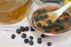 Aronia και μέλι σε ένα πιάτο γυαλιού δίπλα σε ένα βάζο με το μέλι Στοκ εικόνα με δικαίωμα ελεύθερης χρήσης